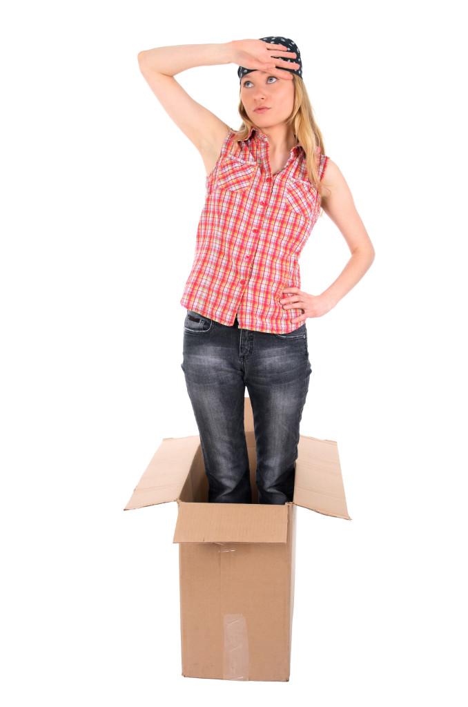 Tired girl standing in a cardboard box